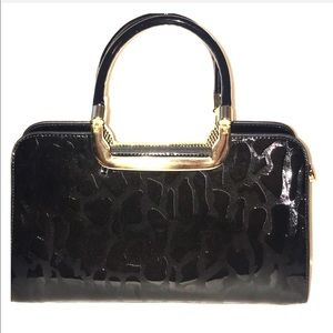 Black patent leather bag with gold hardware.